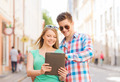 smiling couple with tablet pc in city - PhotoDune Item for Sale