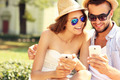 Joyful couple using smartphones in the park - PhotoDune Item for Sale