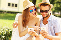 Happy couple sitting on a bench with smartphones - PhotoDune Item for Sale