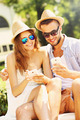 Joyful couple sitting on a bench with smartphones - PhotoDune Item for Sale