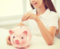 smiling child putting coin into big piggy bank - PhotoDune Item for Sale