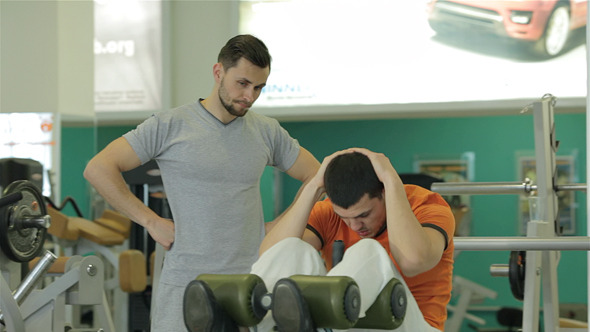 Fitness Trainer Shows a Young Man
