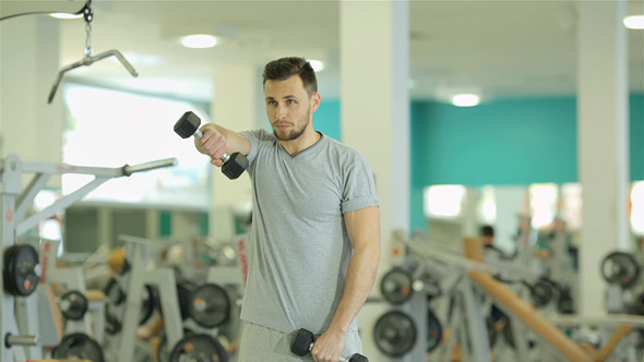 Young Man Doing Exercise With Dumbbells