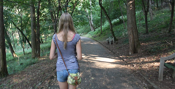 Girl Walking Alone Through the Forest