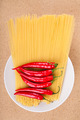 Chili peppers and uncooked pasta on plate - PhotoDune Item for Sale