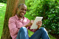 Handsome man with tablet in the park - PhotoDune Item for Sale