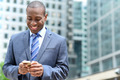 Smiling businessman using his smartphone - PhotoDune Item for Sale