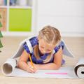 Girl Drawing On Chart Paper While Lying On Hardwood Floor - PhotoDune Item for Sale