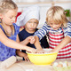 Girl Pouting While Sisters Making Dough In Bowl At Kitchen Count - PhotoDune Item for Sale