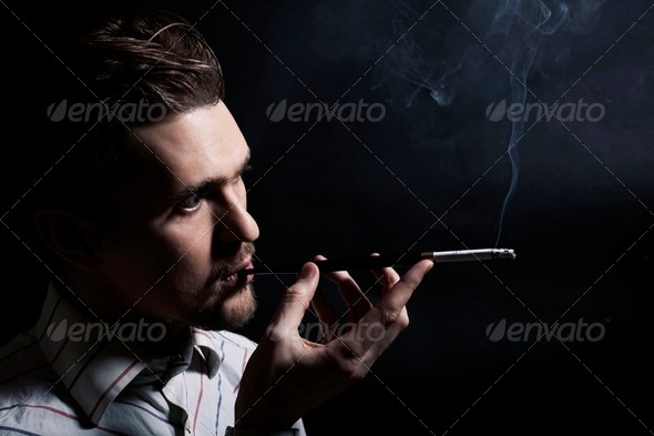 Studio portrait of a young man smoking - Stock Photo - Images