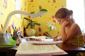 schoolgirl learns lessons at the table - PhotoDune Item for Sale