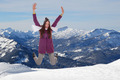 Young woman jumping for joy and happiness in mountains