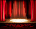 A theater stage with a red curtain, seats and a spotlight. - PhotoDune Item for Sale