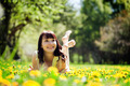 Young beautiful woman lying on grass full of spring flowers and smiling. - PhotoDune Item for Sale