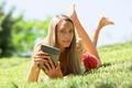 girl lying on grass enjoying reading  ereader - PhotoDune Item for Sale