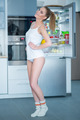 Playful young woman posing in front of her fridge - PhotoDune Item for Sale