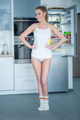 Young woman posing in front of an open fridge - PhotoDune Item for Sale