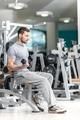 Smiling athlete bodybuilder man at biceps brachii muscles exerci