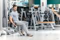 Best body. Smiling athlete bodybuilder man at biceps brachii mus