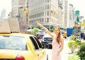Woman hailing Taxi cab in Manhattan New York