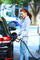Woman refueling her Car at Gas Station