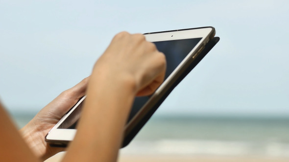Woman Using a Tablet On Beach