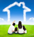 happy family sitting on a meadow with house of clouds in the blue sky - PhotoDune Item for Sale