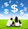 family sitting on a meadow with money of clouds in the blue sky background - PhotoDune Item for Sale