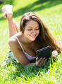 Girl lying on grass with tablet - PhotoDune Item for Sale
