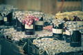 Many preserving jars with dark jam in a market - PhotoDune Item for Sale