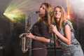 Attractive women playing on saxophone and with microphone at music concert - PhotoDune Item for Sale