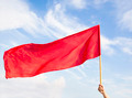 Hand waving a red flag with blue sky and cloud background  - PhotoDune Item for Sale