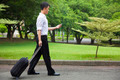 businessman walking and using a phone on the road in the park - PhotoDune Item for Sale