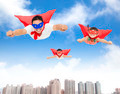 superman and daughters  flying in the sky with buildings background - PhotoDune Item for Sale