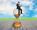 man using smart pad sitting on sandglass - PhotoDune Item for Sale