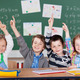 Four little schoolchildren raising their hands - PhotoDune Item for Sale