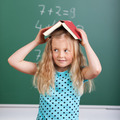 Adorable little girl balancing a book on her head - PhotoDune Item for Sale