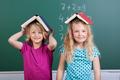 Two little schoolgirls with book hats - PhotoDune Item for Sale