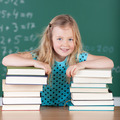 Pretty little blond girl in school with her books - PhotoDune Item for Sale