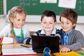 Three young schoolchildren using a laptop - PhotoDune Item for Sale