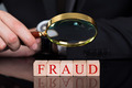 Businessman Examining Fraud Blocks Through Magnifying Glass - PhotoDune Item for Sale