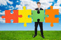 Confident Businessman Solving Jigsaw Puzzle On Field - PhotoDune Item for Sale