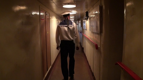 Sailor Passes Through the Ship Corridor