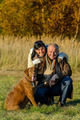 Cheerful couple with dog in autumn park - PhotoDune Item for Sale