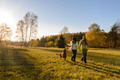 Couple walk dog in countryside autumn sunset - PhotoDune Item for Sale