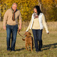 Couple walking dog in autumn sunny park - PhotoDune Item for Sale