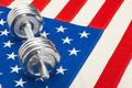 Metal dumbbell over US flag as symbol of healthy nation - studio shot - PhotoDune Item for Sale