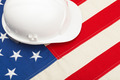 White color construction helmet laying over US flag - PhotoDune Item for Sale