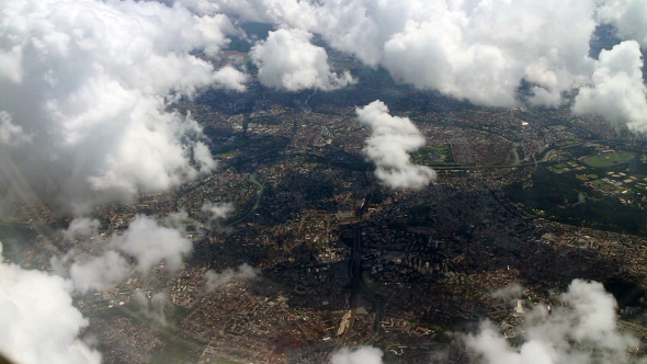 Airplane Flying over City and Clouds 851