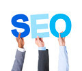 Multiethnic Business People Holding the Word SEO
